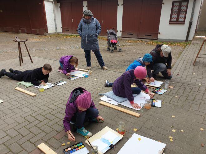 Vollkonzentrierte kleine Künstler auf dem Atelierhof